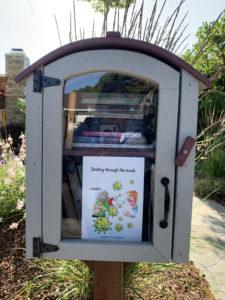 Smiling through the mask in a  neighborhood book box. Palo Alto
